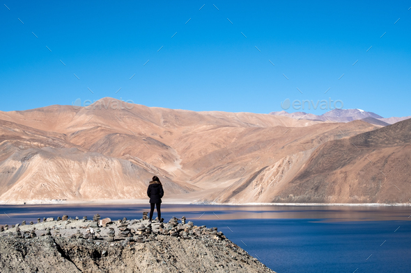 A woman standing in front of Pangong lake with mountains view and blue sky background - Stock Photo - Images