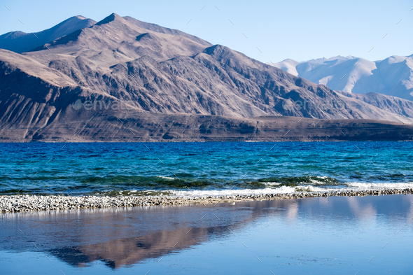 Landscape reflection image of Pangong lake with mountains view and blue sky background - Stock Photo - Images