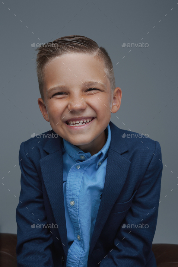 Joyful kid weared in suit posing against gray background - Stock Photo - Images