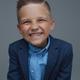 Joyful kid weared in suit posing against gray background - PhotoDune Item for Sale