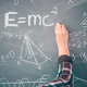 Teacher or student writing on blackboard during math lesson in school classroom - PhotoDune Item for Sale