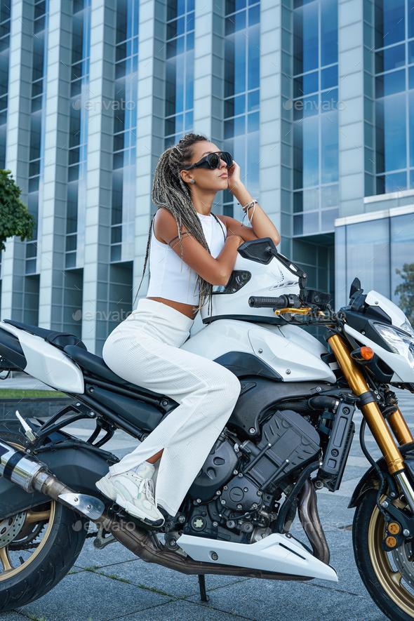 Woman dressed in stylish clothing sitting on motorbike - Stock Photo - Images