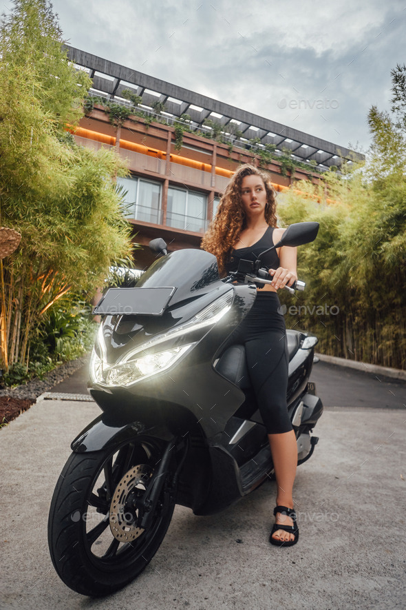 Young sportswoman sitting on bike around modern mansion - Stock Photo - Images