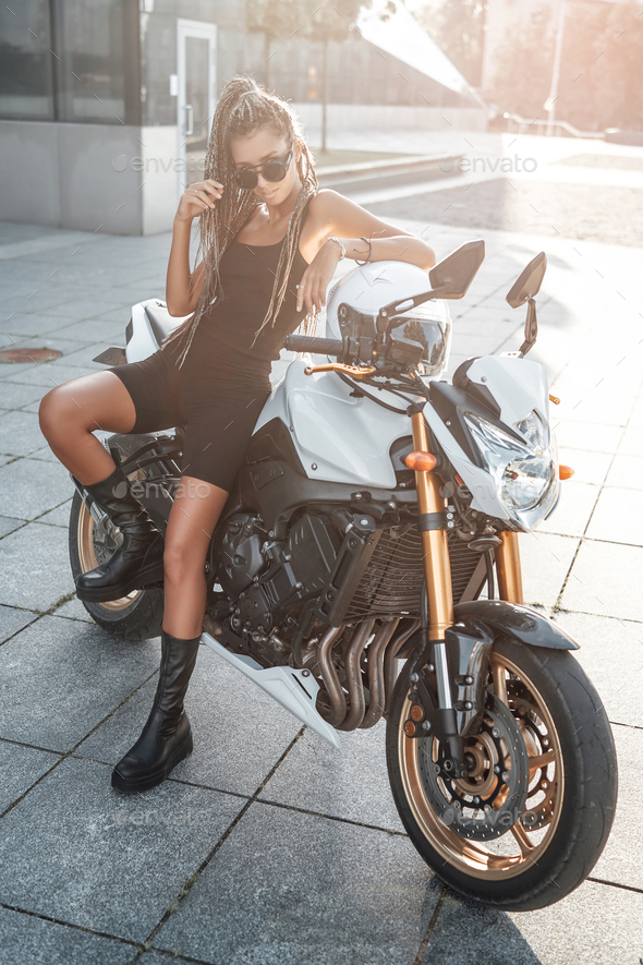 Woman biker with urban motorbike outside on sidewalk - Stock Photo - Images