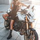Woman biker with urban motorbike outside on sidewalk - PhotoDune Item for Sale