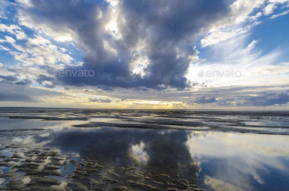 Clouds reflections in the still ocean from the beach, Bay of Saint Michel in Normandy - Stock Photo - Images