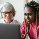 Diverse senior and young woman having video call on computer at home office - Focus on african girl - PhotoDune Item for Sale