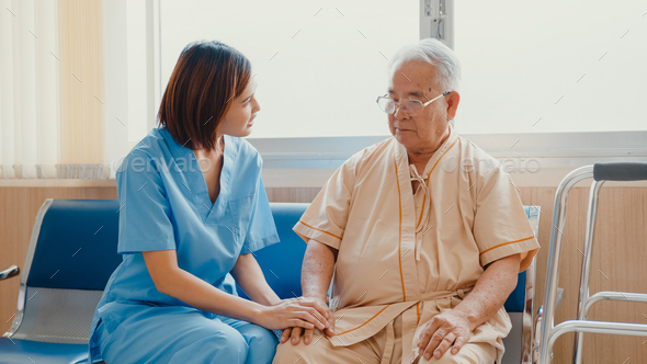 Young Asian woman nurse caregiver encourage take care her senior patient hold hand explain. - Stock Photo - Images