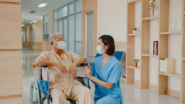 Young Asian woman nurse caregiver wear medical face mask encourage take care her patient explain. - Stock Photo - Images
