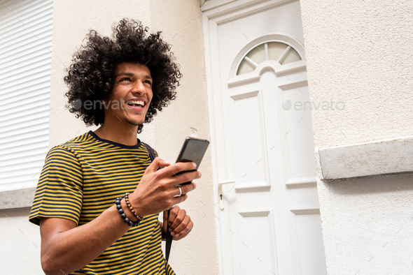 Close up happy young man walking with cellphone in city - Stock Photo - Images