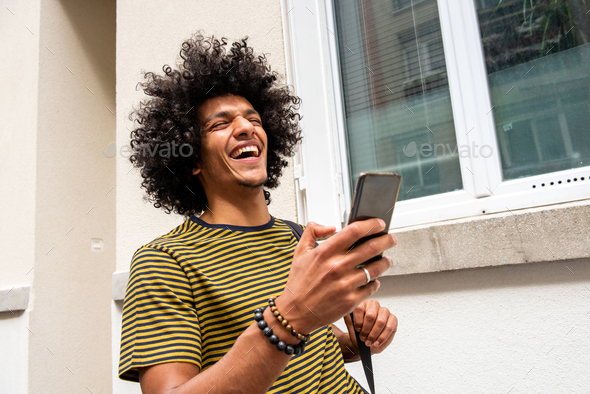 Close up laughing young man walking with cellphone in city - Stock Photo - Images