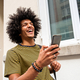 Close up laughing young man walking with cellphone in city - PhotoDune Item for Sale