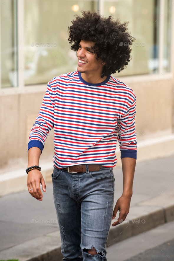 cool young arabic man walking on city street - Stock Photo - Images