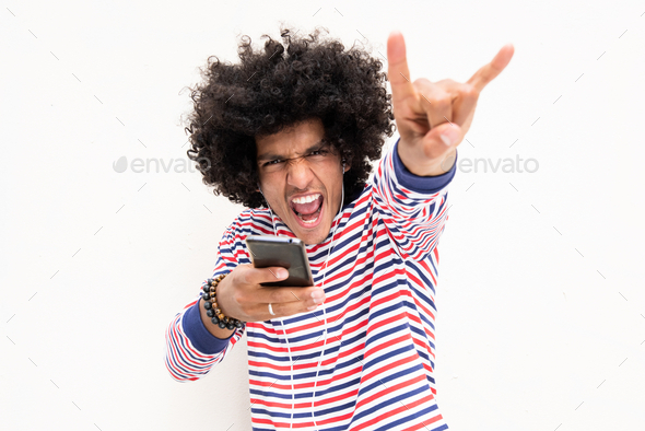 young man listening to music with mobile phone and earphones giving hand gesture - Stock Photo - Images