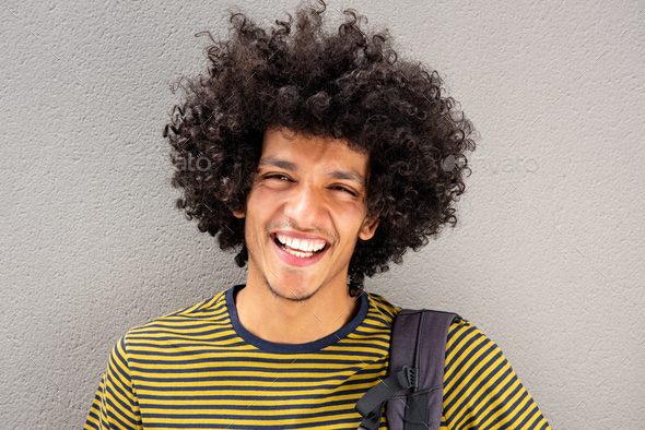 Close up portrait smiling young man with afro against white wall - Stock Photo - Images
