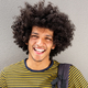 Close up portrait smiling young man with afro against white wall - PhotoDune Item for Sale