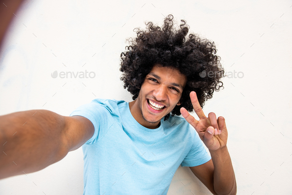 Close up happy young man with afro hair taking selfie by isolated white background - Stock Photo - Images