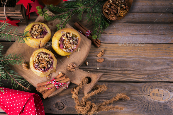 Baked apples stuffed with berries, walnuts and honey on a wooden cutting board. - Stock Photo - Images