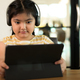 The girl is wearing headphones intently looking at the tablet - PhotoDune Item for Sale