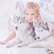 Beautiful blonde woman sits with two husky dogs near christmas tree. - PhotoDune Item for Sale