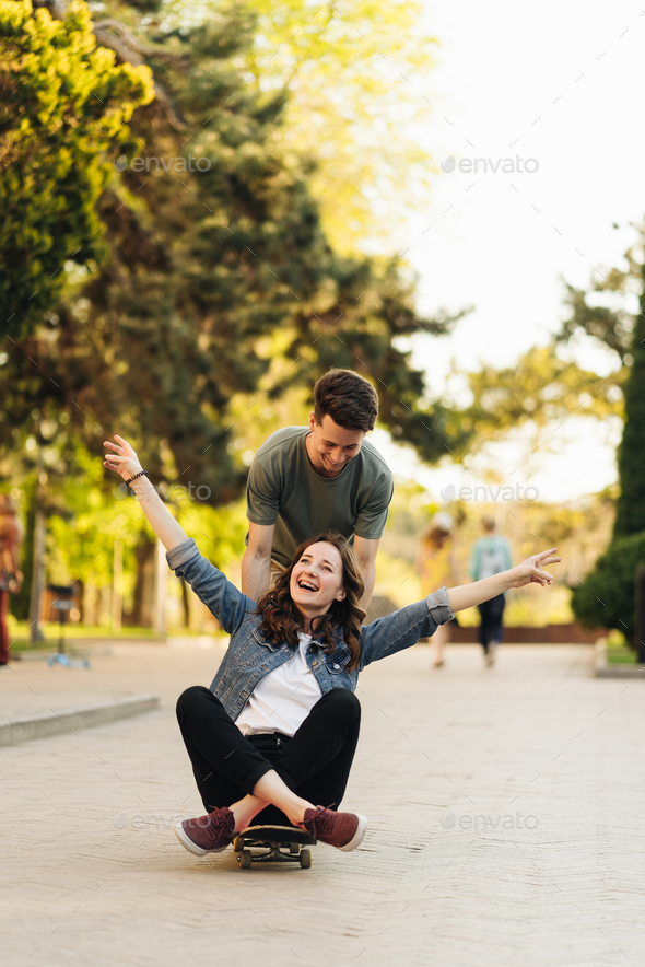 Young Couple practicing skateboarding outdoors - Stock Photo - Images