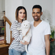 Happy young Caucasian pretty wife and African husband with cute cat animal - PhotoDune Item for Sale