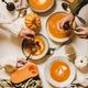 Flat-lay of womens hands eating fall pumpkin cream soup - PhotoDune Item for Sale