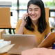 A woman selling an online product talks on the phone for information and holds a customer file. - PhotoDune Item for Sale