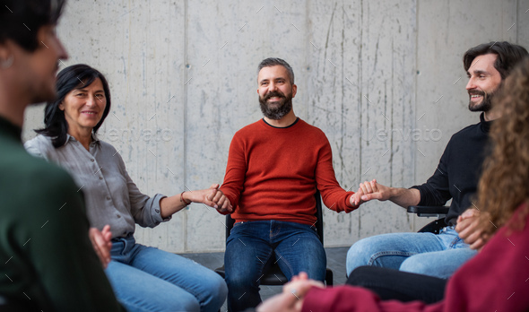 Men and women sitting in circle during group therapy, holding hands - Stock Photo - Images