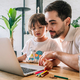 Little boy and his father using a laptop at home. - PhotoDune Item for Sale