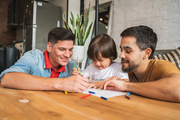 Gay couple having fun with their son at home. - Stock Photo - Images