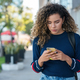 Latin woman using a mobile phone while walking outdoors on the street. - PhotoDune Item for Sale