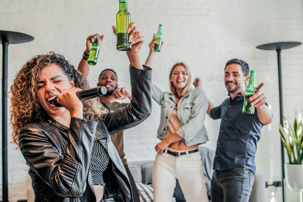 Group of friends playing karaoke at home. - Stock Photo - Images