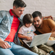 Two fathers enjoy wathching movies with their son at home. - PhotoDune Item for Sale