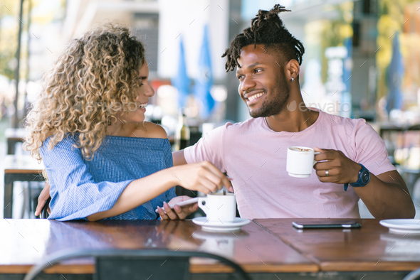 Young couple drinking coffee at a coffee shop. - Stock Photo - Images