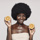 Portrait of beautiful young African woman holding orange pieces and smiling - PhotoDune Item for Sale