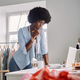 Beautiful young African woman holding pencil and looking thoughtful while standing near her desk - PhotoDune Item for Sale