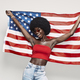 Happy young African woman carrying American flag and smiling while standing against gray background - PhotoDune Item for Sale