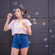 Stylish teen girl blowing soap bubbles - PhotoDune Item for Sale