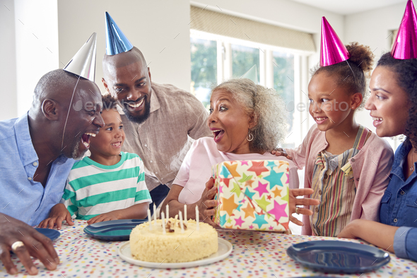 Multi Generation Family Around Table At Home Celebrating Grandmother's Birthday With Cake And Party - Stock Photo - Images