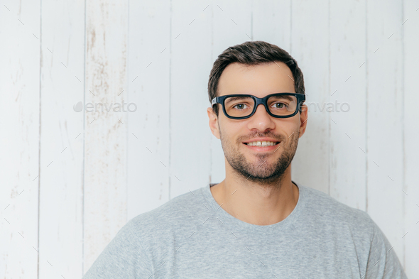 Handsome male with dark hair, wears spectacles, has gentle smile, looks directly into camera - Stock Photo - Images