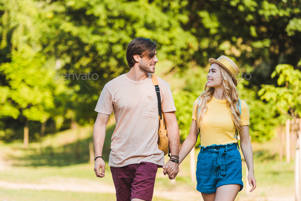 portrait of happy couple in love walking in summer park together - Stock Photo - Images