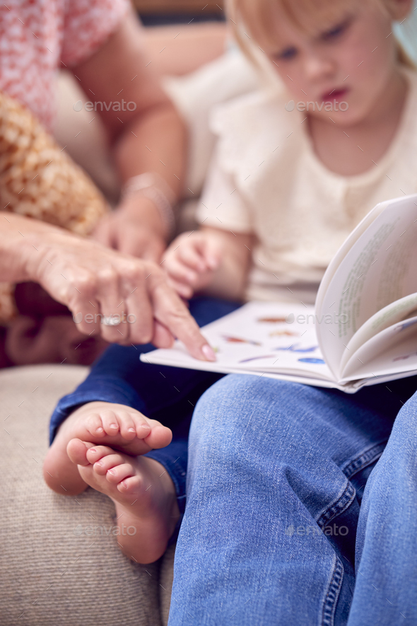 Close Up Of Grandparents Sitting On Sofa With Granddaughter At Home Reading Book Together - Stock Photo - Images
