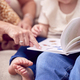 Close Up Of Grandparents Sitting On Sofa With Granddaughter At Home Reading Book Together - PhotoDune Item for Sale