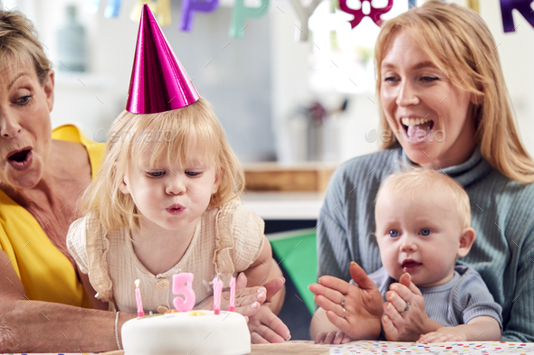 Grandmother With Mother And Grandchildren Celebrating With Fifth Birthday Party At Home - Stock Photo - Images