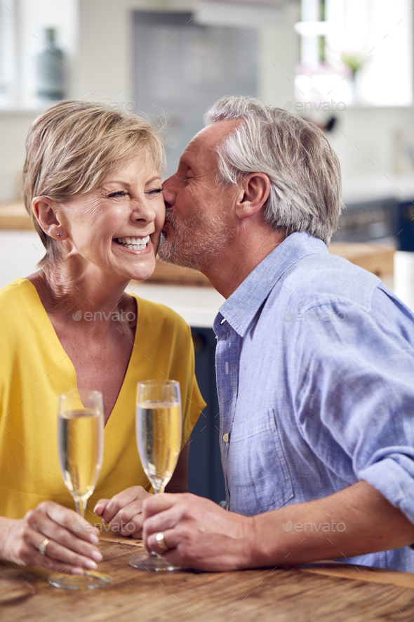 Kissing Retired Couple Celebrating With Glass Of Champagne At Home On Date Night Together - Stock Photo - Images
