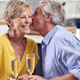 Kissing Retired Couple Celebrating With Glass Of Champagne At Home On Date Night Together - PhotoDune Item for Sale