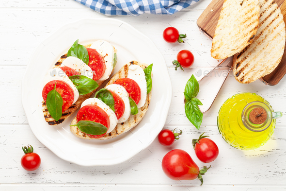Caprese salad with mozzarella, basil and garden tomatoes - Stock Photo - Images