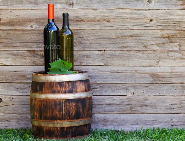 Wine bottles on wine barrel - Stock Photo - Images