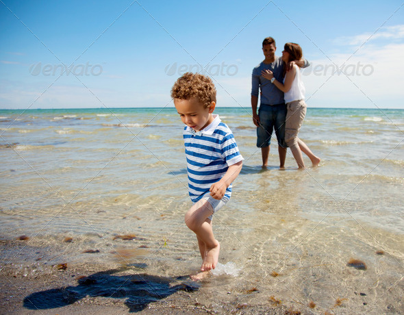 Young Couple Watches as Son Walks Away from the Water - Stock Photo - Images